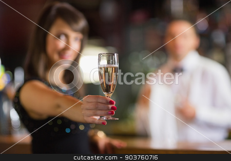 Pretty brunette smiling at camera with champagne stock photo, Pretty brunette smiling at camera with champagne in a bar by Wavebreak Media