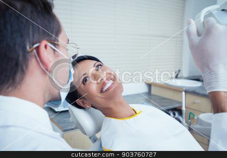 Smiling woman waiting for dental exam stock photo, Side view of smiling young woman waiting for a dental exam by Wavebreak Media