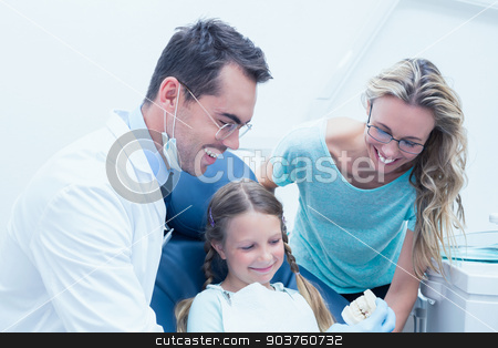 Happy male dentist with assistant and girl stock photo, Portrait of happy male dentist with assistant and little girl by Wavebreak Media