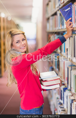 Mature student picking out book in library stock photo, Mature student picking out book in library at the university by Wavebreak Media