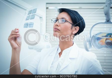 Female dentist looking at x-ray stock photo, Concentrated female dentist looking at x-ray by Wavebreak Media