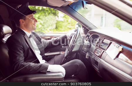 Limousine driver driving and smiling stock photo, Limousine driver driving and smiling in his limousine by Wavebreak Media