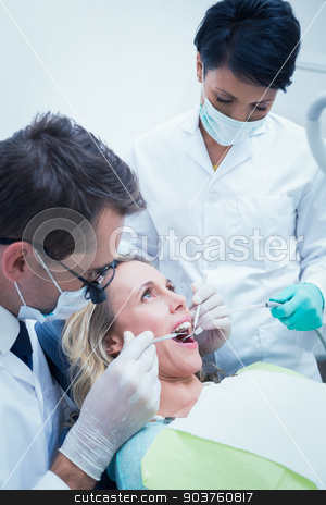 Male dentist with assistant examining womans teeth stock photo, Close up of male dentist with assistant examining womans teeth in the dentists chair by Wavebreak Media