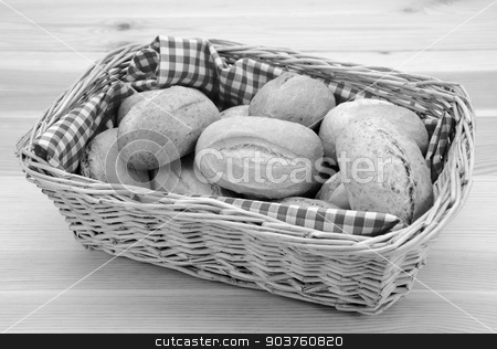 Basket full of fresh bread rolls stock photo, Wicker basket full of crusty bread rolls on a wooden table - monochrome processing by Sarah Marchant