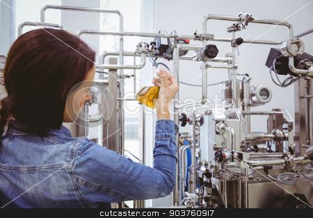 Stylish girl in denim jacket holding beaker of beer  stock photo, Stylish girl in denim jacket holding beaker of beer in the factory by Wavebreak Media