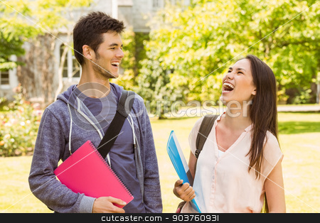 Smiling friends student standing with shoulder bag holding book stock photo, Smiling friends student standing with shoulder bag holding book in park at school by Wavebreak Media