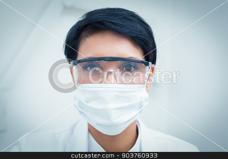 Dentist wearing surgical mask and safety glasses stock photo, Portrait of female dentist wearing surgical mask and safety glasses by Wavebreak Media
