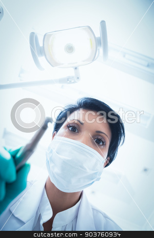 Female dentist in surgical mask holding dental drill stock photo, Low angle view of female dentist in surgical mask holding dental drill by Wavebreak Media