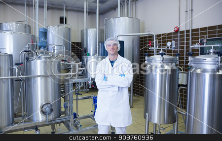 Scientist with arms crossed standing in front of container stock photo, Scientist with arms crossed standing in front of container in the factory by Wavebreak Media