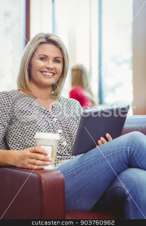 Smiling girl using digital tablet and holding disposable cup stock photo, Smiling girl using digital tablet and holding disposable cup in library by Wavebreak Media