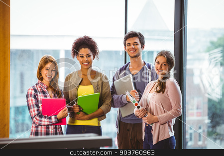 Four smiling classmates standing in front of the window stock photo, Four smiling classmates standing in front of the window in library by Wavebreak Media