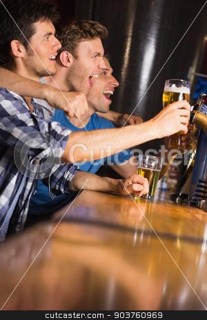 Happy friends catching up over pints stock photo, Happy friends catching up over pints in a bar by Wavebreak Media