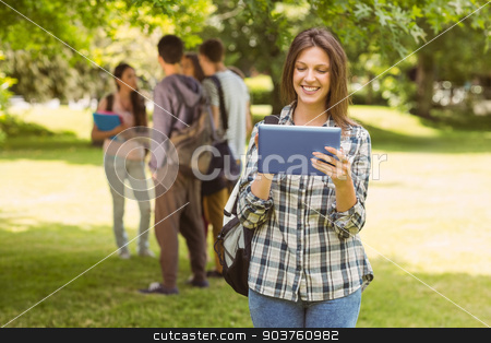 Smiling student with a shoulder bag and using tablet computer stock photo, Smiling student with a shoulder bag and using tablet computer in park at school by Wavebreak Media