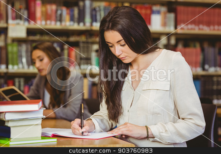 Concentrating pretty brunette student writing in notepad stock photo, Concentrating pretty brunette student writing in notepad in library by Wavebreak Media