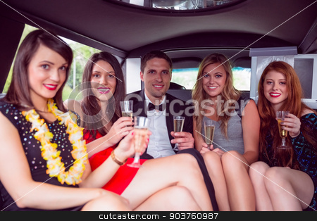 Happy friends drinking champagne in limousine stock photo, Happy friends drinking champagne in limousine on a night out by Wavebreak Media