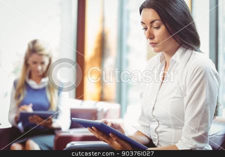 Thoughtful businesswomen using digital tablet stock photo, Thoughtful businesswomen using digital tablet in the office by Wavebreak Media