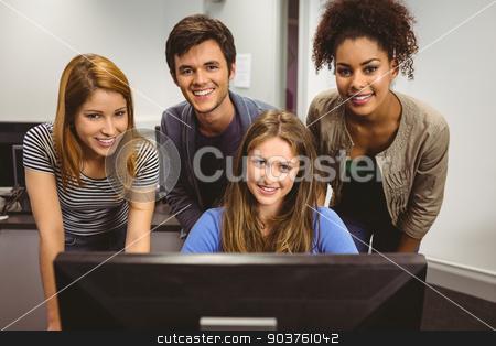 Smiling students using computer together looking at camera stock photo, Smiling students using computer together looking at camera in classroom by Wavebreak Media