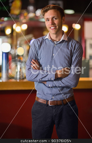 Handsome young man smiling with arms crossed stock photo, Handsome young man smiling with arms crossed in a bar by Wavebreak Media