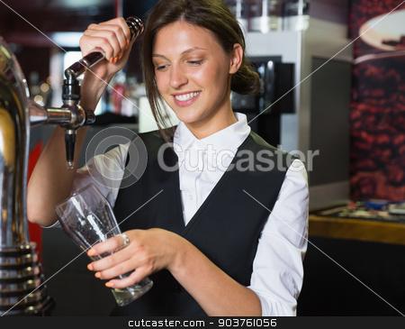 Happy barmaid pulling a pint of beer stock photo, Happy barmaid pulling a pint of beer in a bar by Wavebreak Media