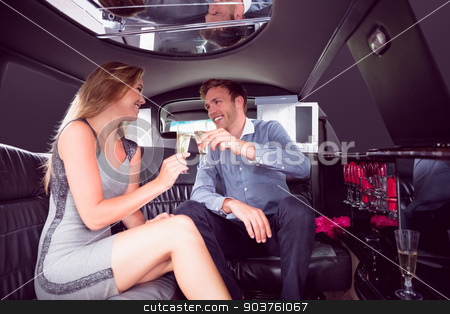 Happy couple drinking champagne in limousine stock photo, Happy couple drinking champagne in limousine on a night out by Wavebreak Media
