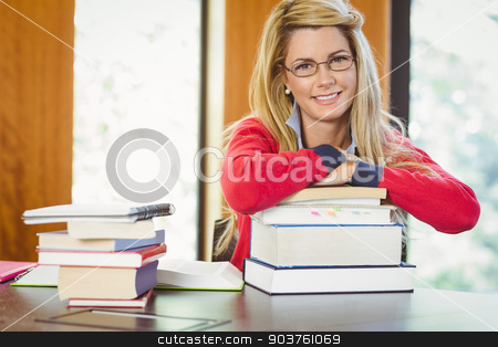 Smiling mature student with stack of books stock photo, Smiling mature student with stack of books in library by Wavebreak Media