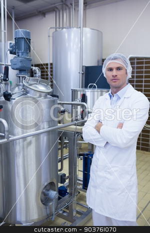 Unsmiling biologist with arms crossed stock photo, Unsmiling biologist with arms crossed in the factory by Wavebreak Media
