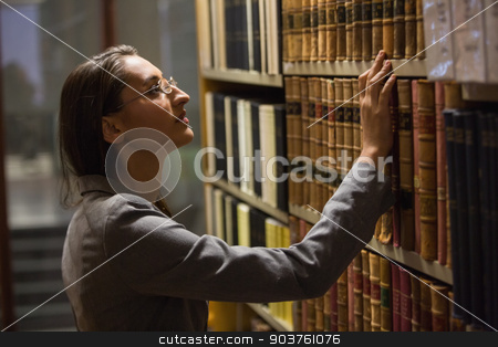 Lawyer picking book in the law library stock photo, Lawyer picking book in the law library at the university by Wavebreak Media