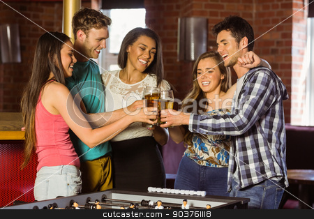 Portrait of happy friends toasting with mixed drink and beer stock photo, Portrait of happy friends toasting with mixed drink and beer in a bar  by Wavebreak Media
