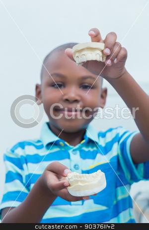 Portrait of boy holding mouth model stock photo, Portrait of smiling young boy holding mouth model by Wavebreak Media