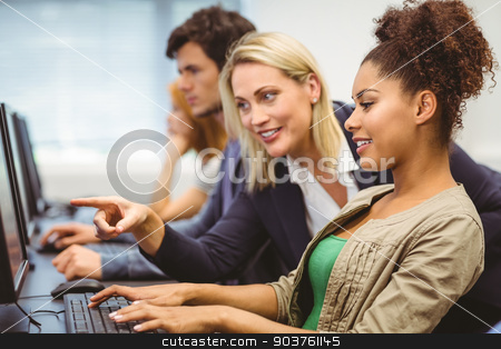 Attractive teacher talking to her student in computer class stock photo, Attractive teacher talking to her student in computer class at the university by Wavebreak Media