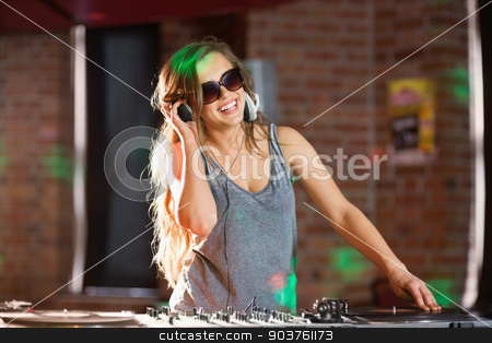 Pretty dj playing techno music stock photo, Pretty dj playing techno music at the nightclub by Wavebreak Media
