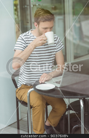 Smiling student drinking hot drink stock photo, Smiling student drinking hot drink in cafe at the university by Wavebreak Media