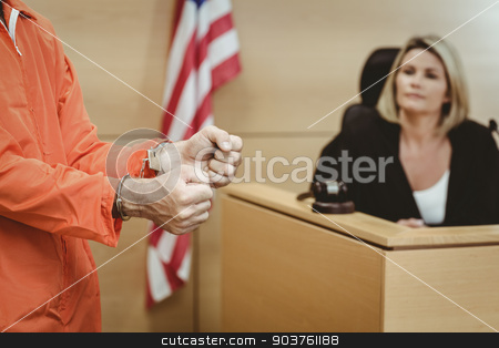 Close up of a prisoner wearing handcuffs stock photo, Close up of a prisoner wearing handcuffs in the court room by Wavebreak Media