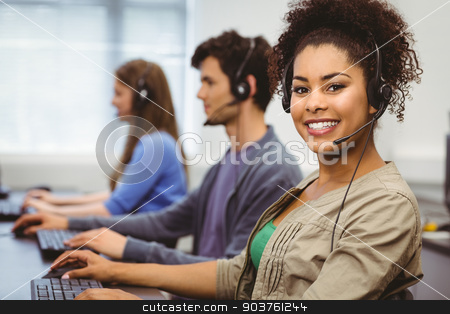 Smiling student with headset using computer stock photo, Smiling student with headset using computer at the university by Wavebreak Media