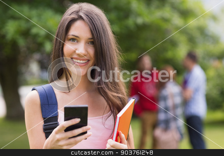 Pretty student sending a text outside on campus stock photo, Pretty student sending a text outside on campus at the university by Wavebreak Media