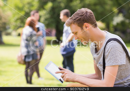 Handsome student studying outside on campus stock photo, Handsome student studying outside on campus at the university by Wavebreak Media
