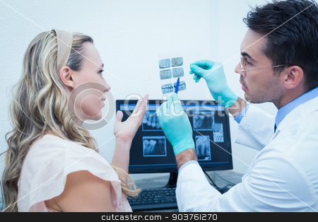 Dentist showing woman her mouth x-ray stock photo, Side view of male dentist showing woman her mouth x-ray by Wavebreak Media