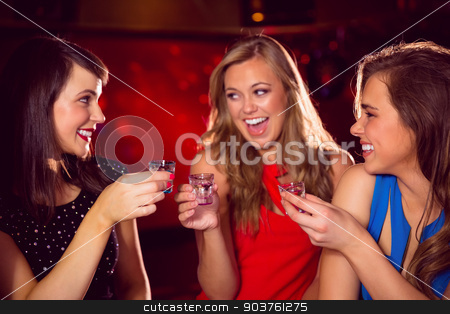 Pretty friends drinking shots together stock photo, Pretty friends drinking shots together at the nightclub  by Wavebreak Media
