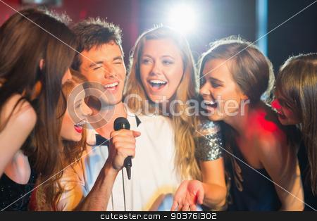 Happy friends singing karaoke together stock photo, Happy friends singing karaoke together in a bar by Wavebreak Media