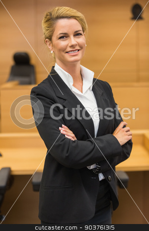 Smiling lawyer looking at camera stock photo, Smiling lawyer looking at camera in the court room by Wavebreak Media
