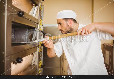 Baker taking bread out of oven stock photo, Baker taking bread out of oven in a commercial kitchen by Wavebreak Media