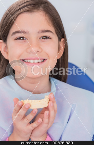 Smiling young patient holding teeth stock photo, Smiling young patient holding teeth in dental clinic by Wavebreak Media