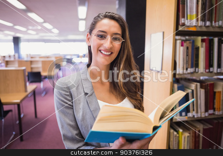Pretty student reading book in library stock photo, Pretty student reading book in library at the university by Wavebreak Media