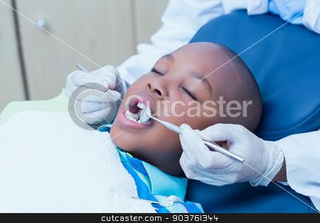Close up of boy having his teeth examined stock photo, Close up of boy having his teeth examined by a dentist by Wavebreak Media