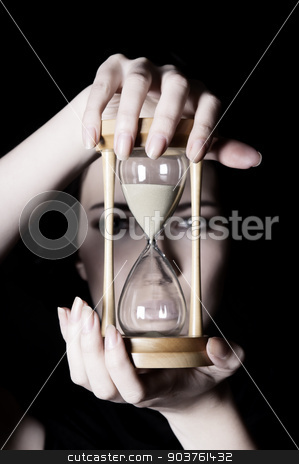Time concept stock photo, young beautiful girl holding an hourglass in front on a black background by Suchota