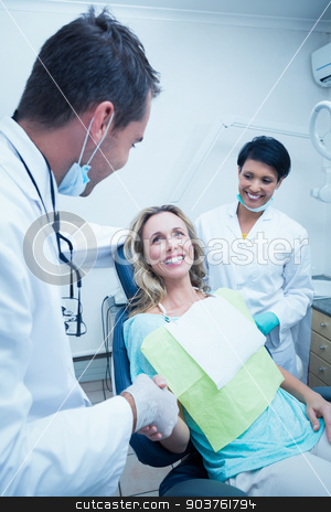 Dentist with assistant shaking hands with woman stock photo, Male dentist with assistant shaking hands with woman in the dentists chair by Wavebreak Media