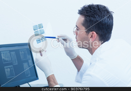Concentrated male dentist looking at x-ray stock photo, Side view of concentrated male dentist looking at x-ray by Wavebreak Media