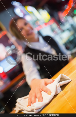 Pretty barmaid wiping down bar stock photo, Pretty barmaid wiping down bar in a bar by Wavebreak Media