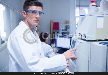 Unsmiling young chemist using the machine stock photo, Unsmiling young chemist using the machine in the laboratory by Wavebreak Media