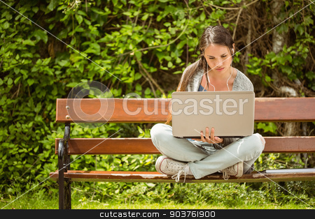 Student sitting on bench listening music and using laptop stock photo, Student sitting on bench listening to music and using laptop and wearing headphones by Wavebreak Media
